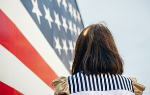 USA, back view of woman in front of Stars And Stripesの写真素材 [FYI04336623]