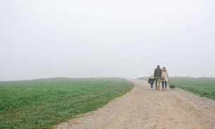 Family walking with dog on a path on a foggy winter dayの写真素材 [FYI04336625]