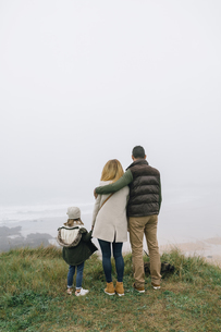 Family with dog at the coast on a foggy winter day looking aの写真素材 [FYI04336627]
