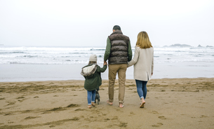 Family walking with dog on the beach in winterの写真素材 [FYI04336636]