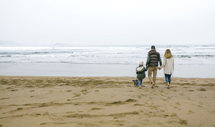Family walking with dog on the beach in winterの写真素材 [FYI04336637]