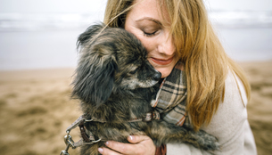 Woman hugging her dog on the beach in winterの写真素材 [FYI04336639]