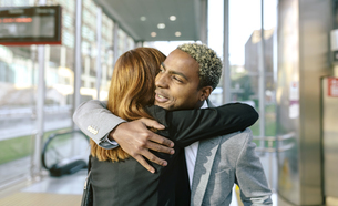 Young businessman and woman embracing at metro stationの写真素材 [FYI04336641]