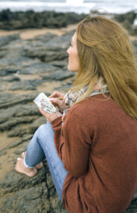 Woman with notebook sitting on rocks on the beach in winterの写真素材 [FYI04336643]