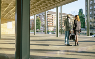 Young businessman and woman talking by office buildingの写真素材 [FYI04336650]