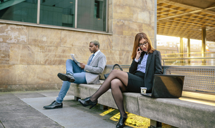 Young businessman and woman sitting on bench, woman talkingの写真素材 [FYI04336662]