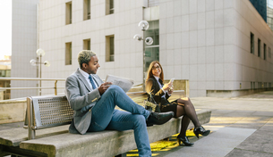 Young businessman and woman sitting on bench, talkingの写真素材 [FYI04336663]