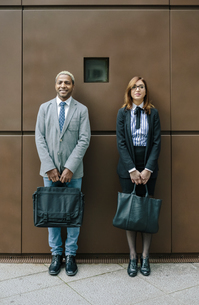 Young businessman and woman standing in front of steel wallの写真素材 [FYI04336668]