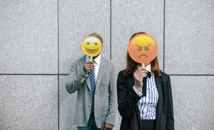Young businessman and woman covering faces with emoji masksの写真素材 [FYI04336670]