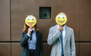 Young businessman and woman covering faces with emoji masksの写真素材 [FYI04336671]