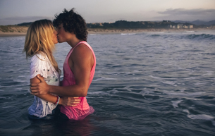 Young couple kissing in the sea at duskの写真素材 [FYI04336674]