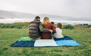 Back view of family with dog sitting on blanket at the coastの写真素材 [FYI04336681]