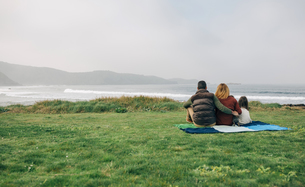 Back view of family with dog sitting on blanket at the coastの写真素材 [FYI04336682]