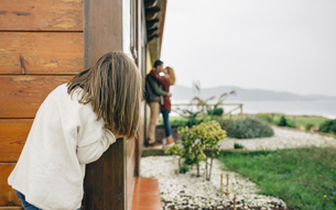 Back view of little girl spying couple in love kissing nextの写真素材 [FYI04336684]