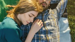 Young couple lying on blanket on a meadowの写真素材 [FYI04336690]