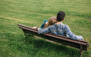 Back view of young couple sitting on bench on a meadowの写真素材 [FYI04336693]