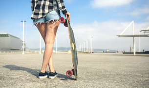 Back view of young woman with longboard in front of beach prの写真素材 [FYI04336695]
