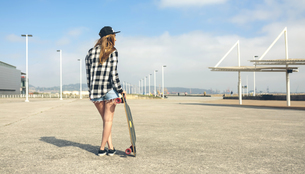 Back view of young woman with longboard standing in front ofの写真素材 [FYI04336696]