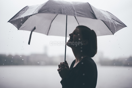 Laughing woman with umbrella on a rainy dayの写真素材 [FYI04336721]