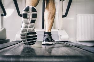 Austria, Klagenfurt, man running on treadmillの写真素材 [FYI04336728]