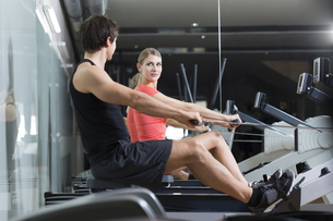 Austria, Klagenfurt, Man and woman exercising with rowing maの写真素材 [FYI04336731]