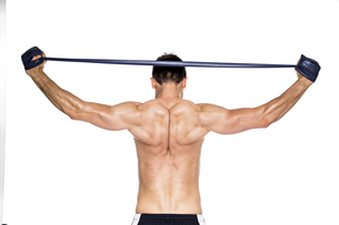 Back view of shirtless muscular man training with fitness baの写真素材 [FYI04336759]