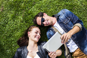 Happy young couple lying in meadow looking at digital tabletの写真素材 [FYI04336761]