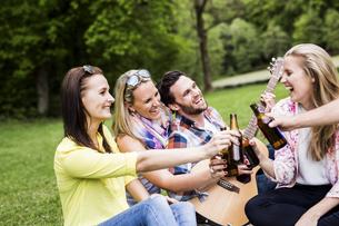 Happy friends clinking beer bottles in parkの写真素材 [FYI04336762]