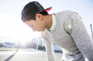 Young man wearing basecap in backlightの写真素材 [FYI04336768]