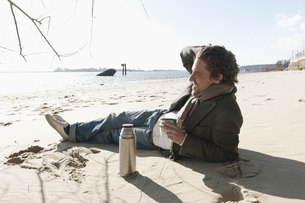Germany, Hamburg, Man lying on sand with coffee flask near Eの写真素材 [FYI04336778]