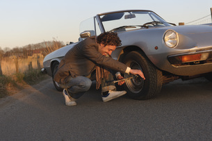 Germany, Hamburg, Man changing tyre of classic cabriolet carの写真素材 [FYI04336780]