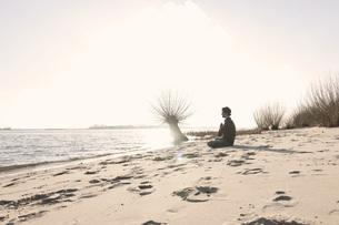 Germany, Hamburg, Man doing yoga exercise near Elbe riversidの写真素材 [FYI04336785]