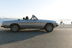 Germany, Hamburg, Man sitting in classic cabriolet car nearの写真素材 [FYI04336788]