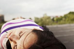 Germany, Hamburg, Young woman lying on wallの写真素材 [FYI04336790]