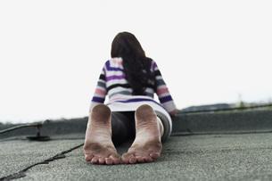 Germany, Hamburg, Young woman lying on roofの写真素材 [FYI04336795]