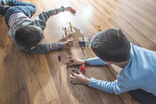 Two boys playing with miniature figurines on the floor at hoの写真素材 [FYI04336806]