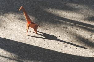 Orange origami giraffe on stone floorの写真素材 [FYI04336809]
