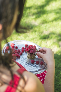 Woman holding metal cup and tray of raspberriesの写真素材 [FYI04336811]