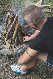 Man lighting a fire on a meadowの写真素材 [FYI04336817]