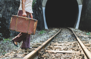 Bulgaria, Woman on railway road and tunnel, suitcase in handの写真素材 [FYI04336818]