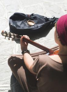 Female street musician playing guitarの写真素材 [FYI04336822]