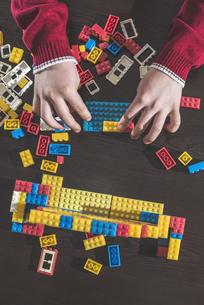 Children's hands playing with building bricks on a tableの写真素材 [FYI04336827]