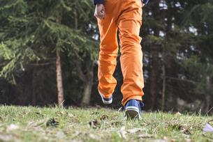 Boy wearing orange trousers walking on a meadowの写真素材 [FYI04336829]