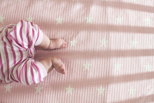 Baby girl lying in a cot, partial viewの写真素材 [FYI04336854]