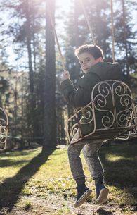 Bulgaria, Rhodope Mountains, portrait of a boy on a swing viの写真素材 [FYI04336855]