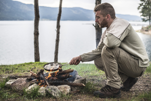 Bulgaria, man frying rudd at camp fire at shore of Dospat Reの写真素材 [FYI04336870]