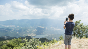 Greece, Central Macedonia, boy taking smartphone picture inの写真素材 [FYI04336874]