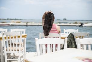 Greece, Lefkada, woman sitting in a Greek taverna by the seaの写真素材 [FYI04336876]