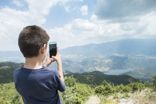 Greece, Central Macedonia, boy taking smartphone picture inの写真素材 [FYI04336877]