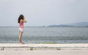 Greece, Amfilochia, woman taking picture at the seaの写真素材 [FYI04336878]